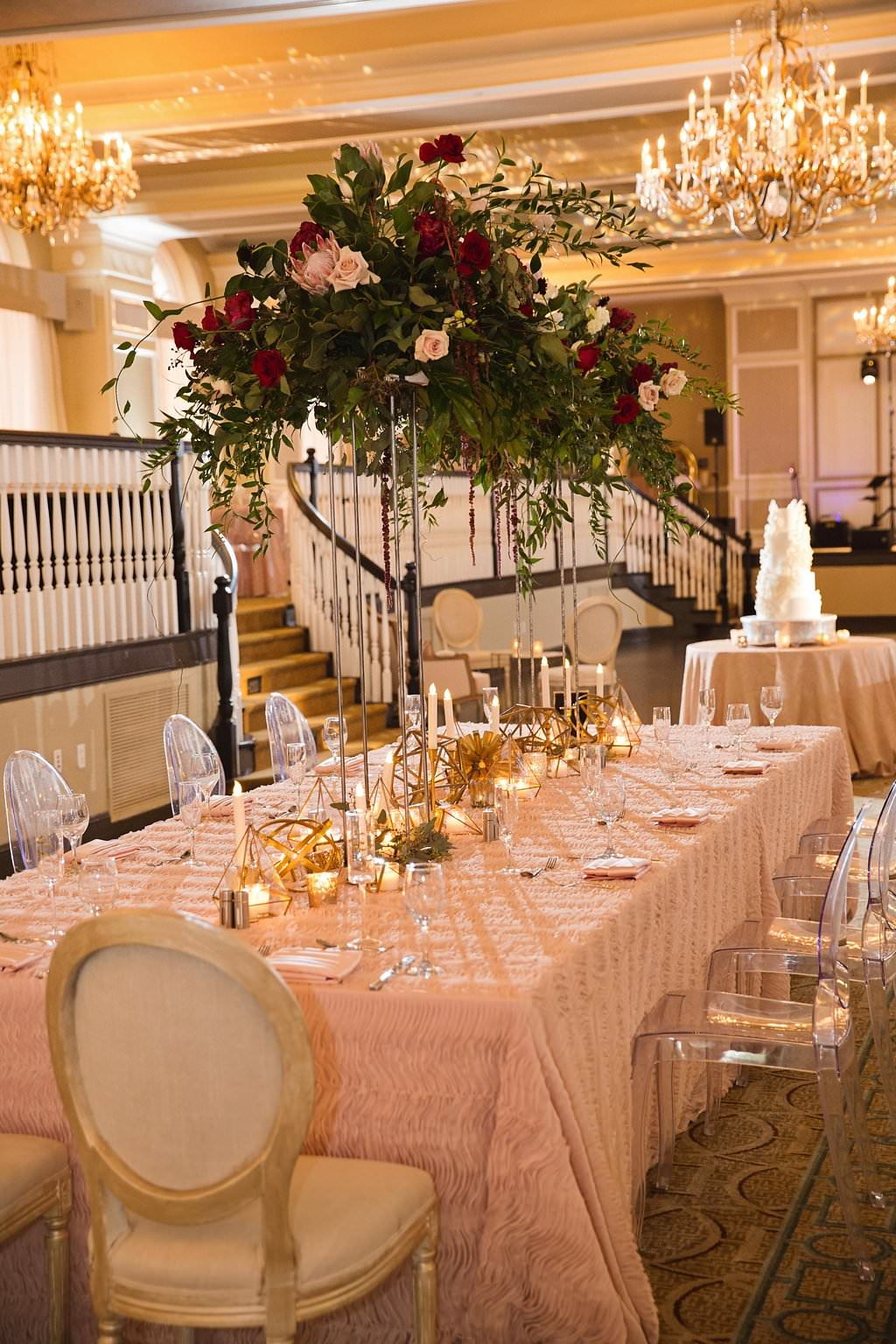 Modern Winter Pink and Burgundy Hotel Ballroom Wedding Reception with Tall Red and Blush Floral with Greenery Centerpiece, Clear Plastic Oval Back Chairs, Textured Blush Linen from Over the Top, and Gold Candles and Accents | Historic Tampa Bay Waterfront Wedding Venue The Don CeSar | St Petersburg Wedding Planner Parties A La Carte |
