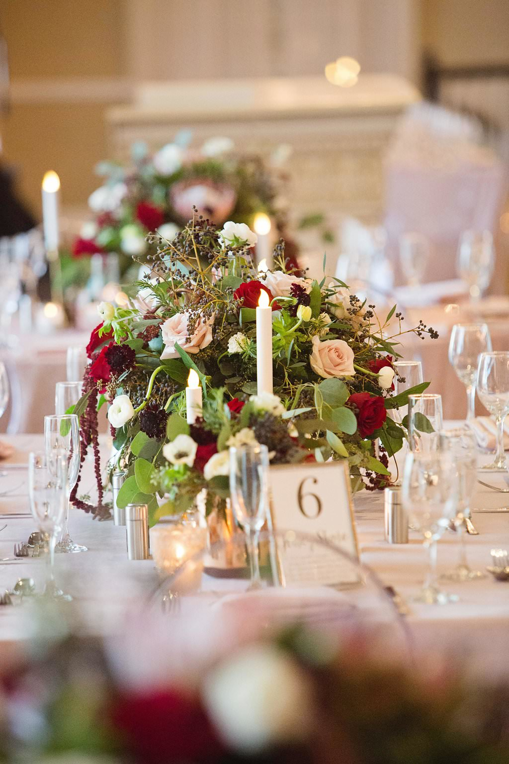 Modern Winter Pink and Burgundy Hotel Ballroom Wedding Reception with Low Red, Blush and Burgundy Floral with Greenery Centerpiece, Blush Linen from Rental Company Over the Top, and Candles | St Petersburg Wedding Planner Parties A La Carte |