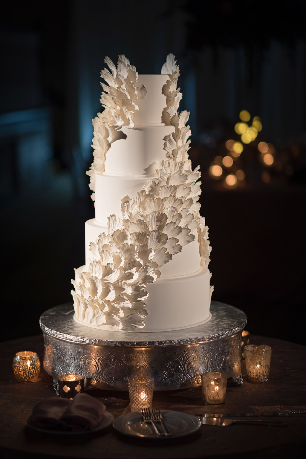 Five Tier Round White Wedding Cake with Feather Wing or Flower Petal Decorations on Silver Cake Stand with Votive Candles