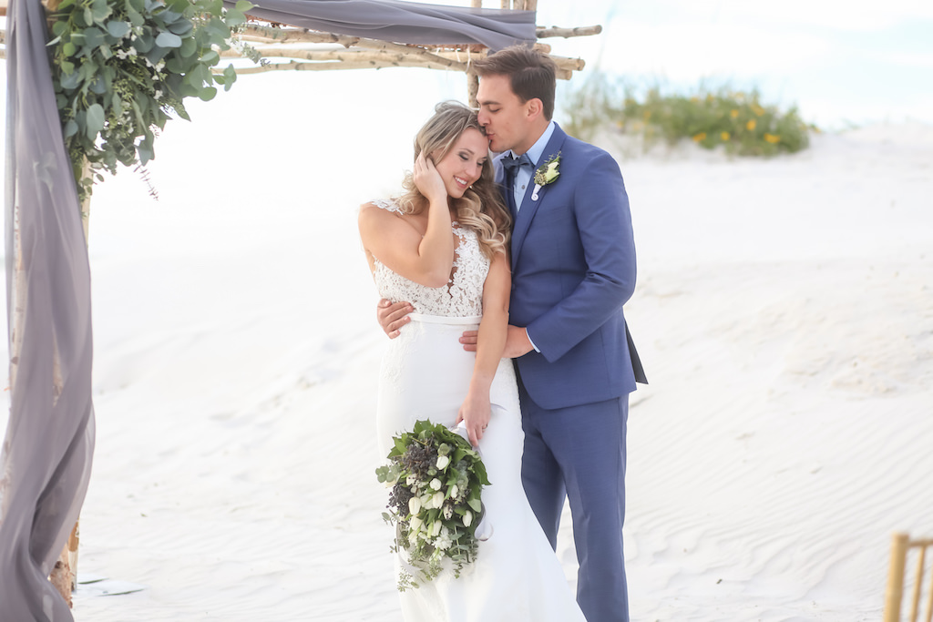 Outdoor Beach Wedding Ceremony Portrait, Bride in Applique Lace Bodice Wedding Dress with White Floral, Blue Berry and Greenery Bouquet, Groom in Blue Suit with Greenery Boutonniere, with Natural Wood Branch Ceremony Arch with Greenery and Gray Draping   Tampa Bay Wedding Photographer Lifelong Photography Studio   Hotel Venue Hilton Clearwater Beach