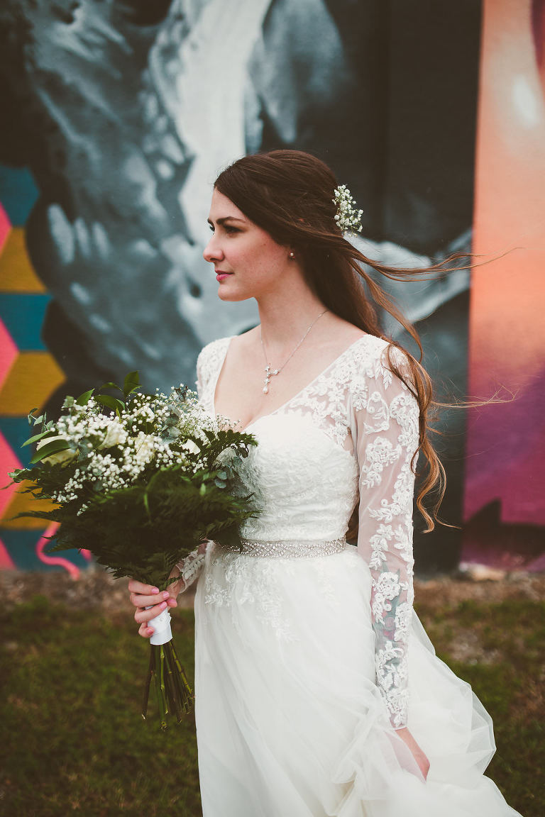 Outdoor Industrial Bridal Portrait in Lace Long Sleeve Belted Davids Bridal Wedding Dress with Green Fern and White Floral Bouquet with Colorful Street Graffiti Mural Art | Downtown St Pete