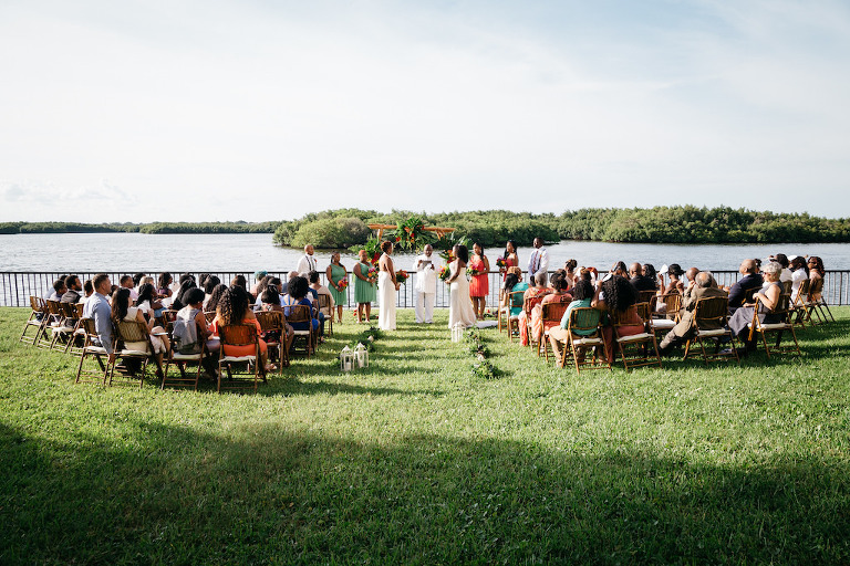 Outdoor Waterfront Wedding Ceremony Portrait with Wooden Folding Chairs, Hurricane Lanterns, and Tropical Floral and Greenery Ceremony Arch, Bridesmaids in Clover Green and Guava Orange Dresses | Tampa Bay Hotel Wedding Venue DoubleTree Suites by Hilton