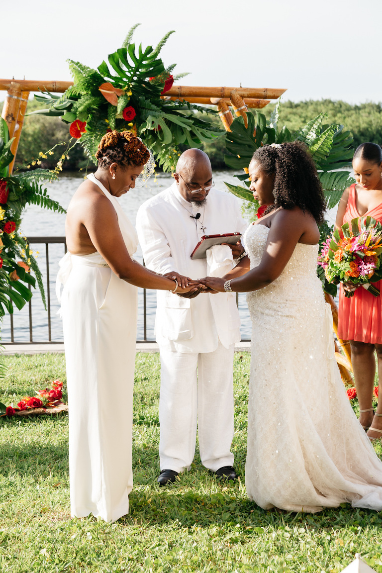 Outdoor Waterfront Wedding Ceremony Portrait, Brides in BHDLN Halter Pantsuit and Strapless Davids Bridal Dress, with Bamboo Ceremony Arch with Red and Orange Florals with Tropical Greenery