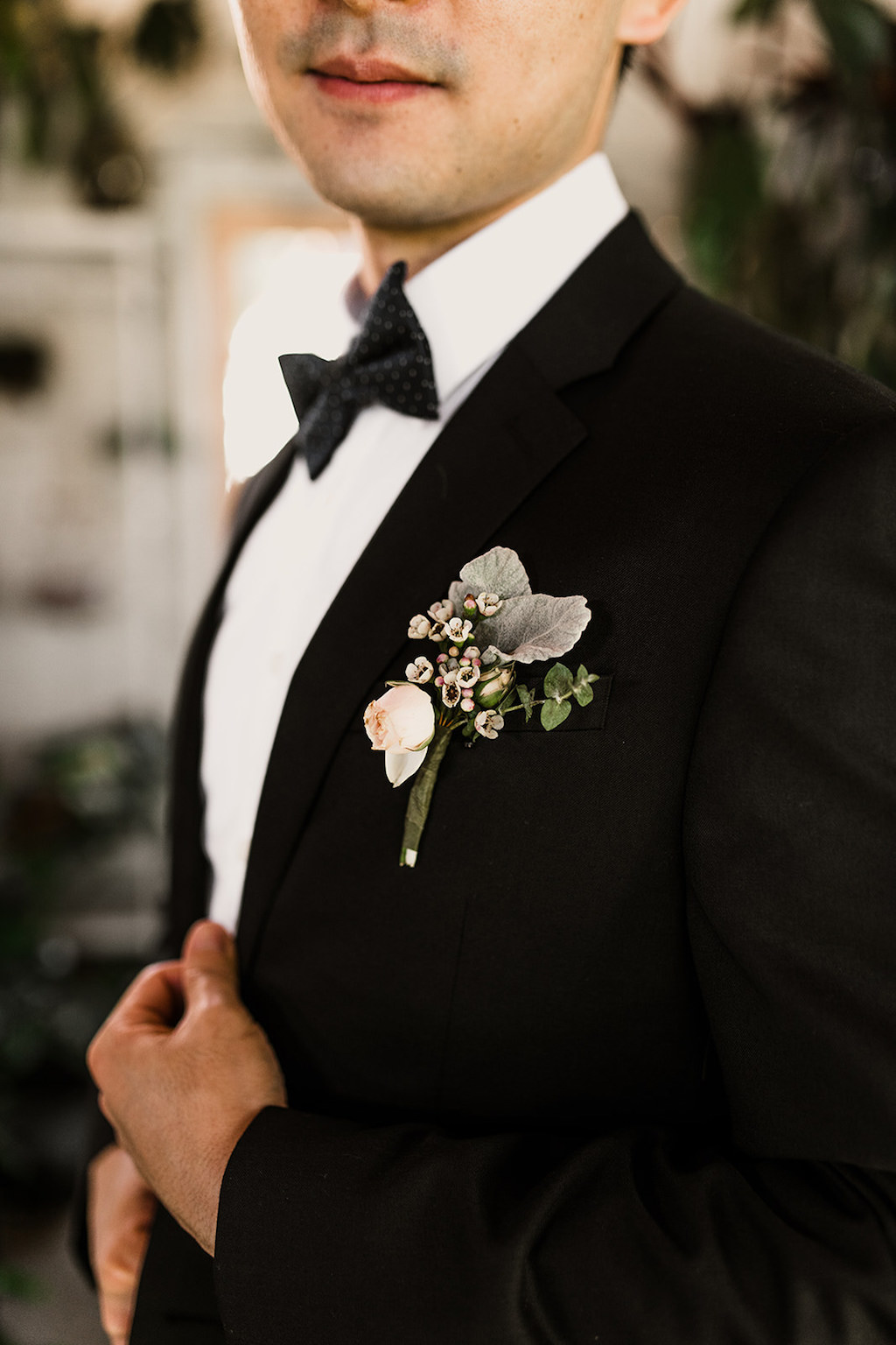 Interior Groom Portrait, wearing Black Tuxedo with Peach and Greenery Floral Boutonniere