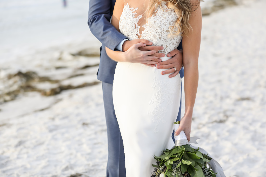 Outdoor Beach Wedding Portrait, Bride in Lace Applique Bodice Dress with Greenery Bouquet with Gray Ribbon, Groom in Blue Suit   Clearwater Beach Wedding Photographer Lifelong Photography Studios