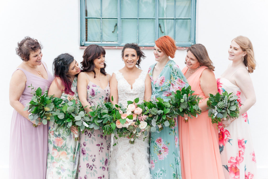 Outdoor Bridal Party Portrait, Bride in V Neck David's Bridal Dress and Peach Floral Bouquet, Bridesmaids in Mismatched Pastel Solid and Floral Print Purple, Pink, and Green Dresses with Greenery Bouquets | St Petersburg Wedding Florist Cotton and Magnolia