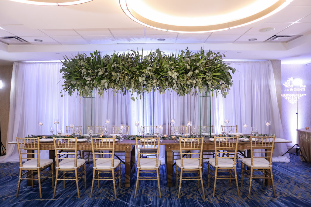 Hotel Ballroom Wedding Reception With Long Wood Feasting Table, Extra Tall Greenery Centerpiece in Clear Glass Rectangular Vases, Gold Chiavari Chairs, White Draping, and Glass Candleholders at Varying Heights   Beach Hotel Wedding Venue Hilton Clearwater Beach