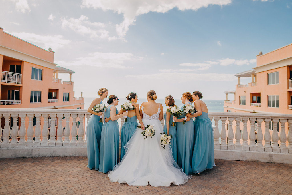 Outdoor Rooftop Bridal Party Portrait, Bridesmaids in Mismatched Light Blue Weddington Way Dresses, Bride in Spaghetti Strap Open Back Layered Ballgown Hayley Paige Wedding Dress, with Ivory Floral with Greenery Bouquets | Tampa Bay Wedding Photographer Rad Red Creative | Waterfront Luxury Hotel Venue Hyatt Regency Clearwater Beach