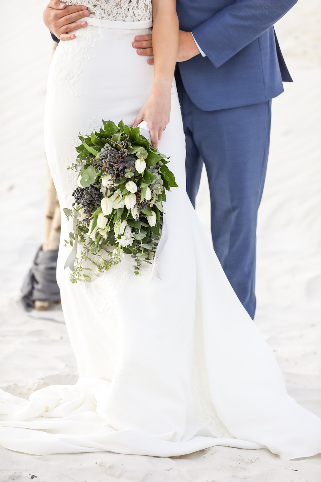 Outdoor Beach Wedding Portrait, Bride in Lace Applique Bodice Dress with Greenery Bouquet with White Tulips and Blue Berries and Greenery, Groom in Blue Suit   Clearwater Beach Wedding Photographer Lifelong Photography Studios
