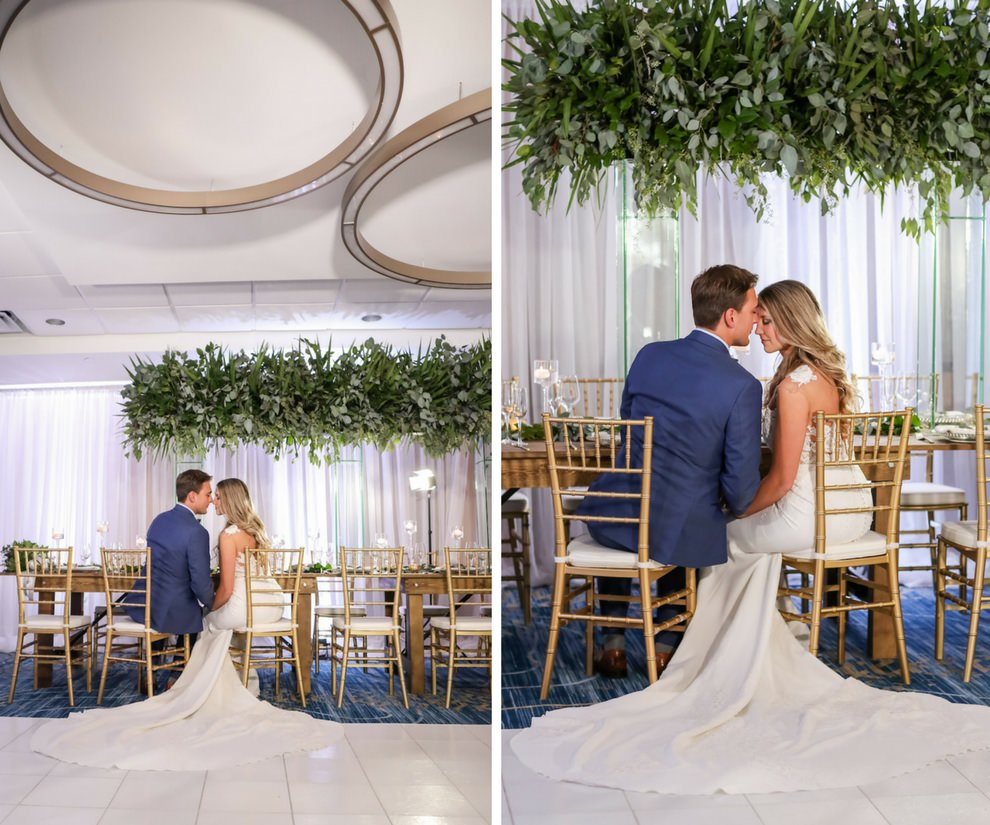 Hotel Ballroom Wedding Reception Portrait With Long Wood Feasting Table, Hanging Greenery Centerpiece, Gold Chiavari Chairs, White Draping, and Glass Candleholders at Varying Heights   Beach Hotel Wedding Venue Hilton Clearwater Beach   Tampa Bay Photographer Lifelong Studios Photography