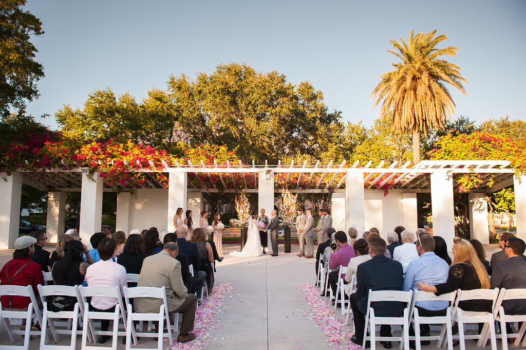 Outdoor Wedding Ceremony Portrait with Pink Rose Petal Aisle and White Folding Chairs, Groomsmen in Light Gray Suits | Downtown St Pete Venue North Straub Park