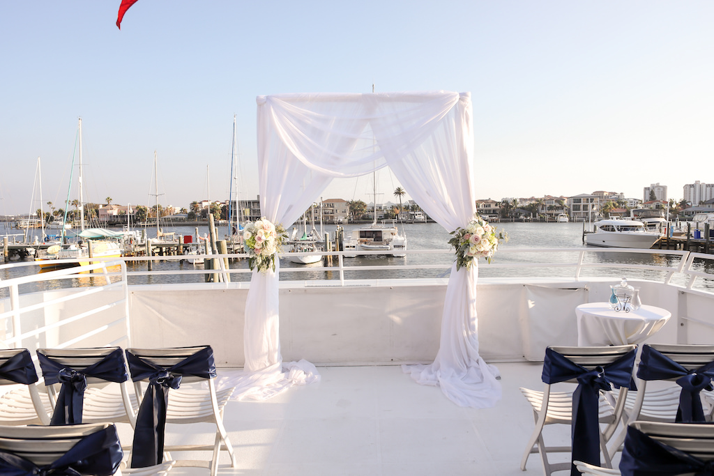Outdoor Waterfront Wedding Ceremony Arch With White Draping Blush Pink And White Rose With Greenery Florals Folding Silver Chairs With Navy Blue Draping Clearwater Beach Unique Wedding Venue Yacht Starship