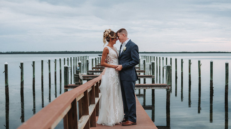 Outdoor Waterfront Wedding Portrait, Groom in Blue Suit with White Rose Boutonniere, Bride in Cutout V Neck Lace Dress | Tampa Bay Wedding Photographer Grind and Press Photography | Dunedin Venue Beso Del Sol
