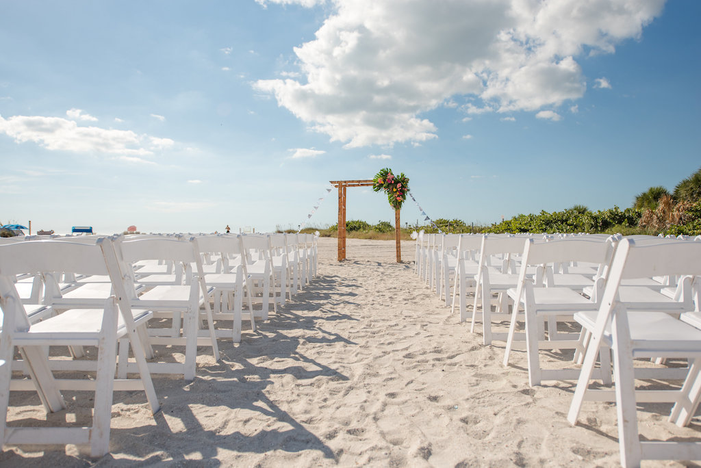 Outdoor Tropical Beach Wedding With White Folding Chairs And Bamboo Ceremony Arch With Pink And Yellow Florals With Greenery St Pete Beach Venue Postcard Inn Marry Me Tampa Bay