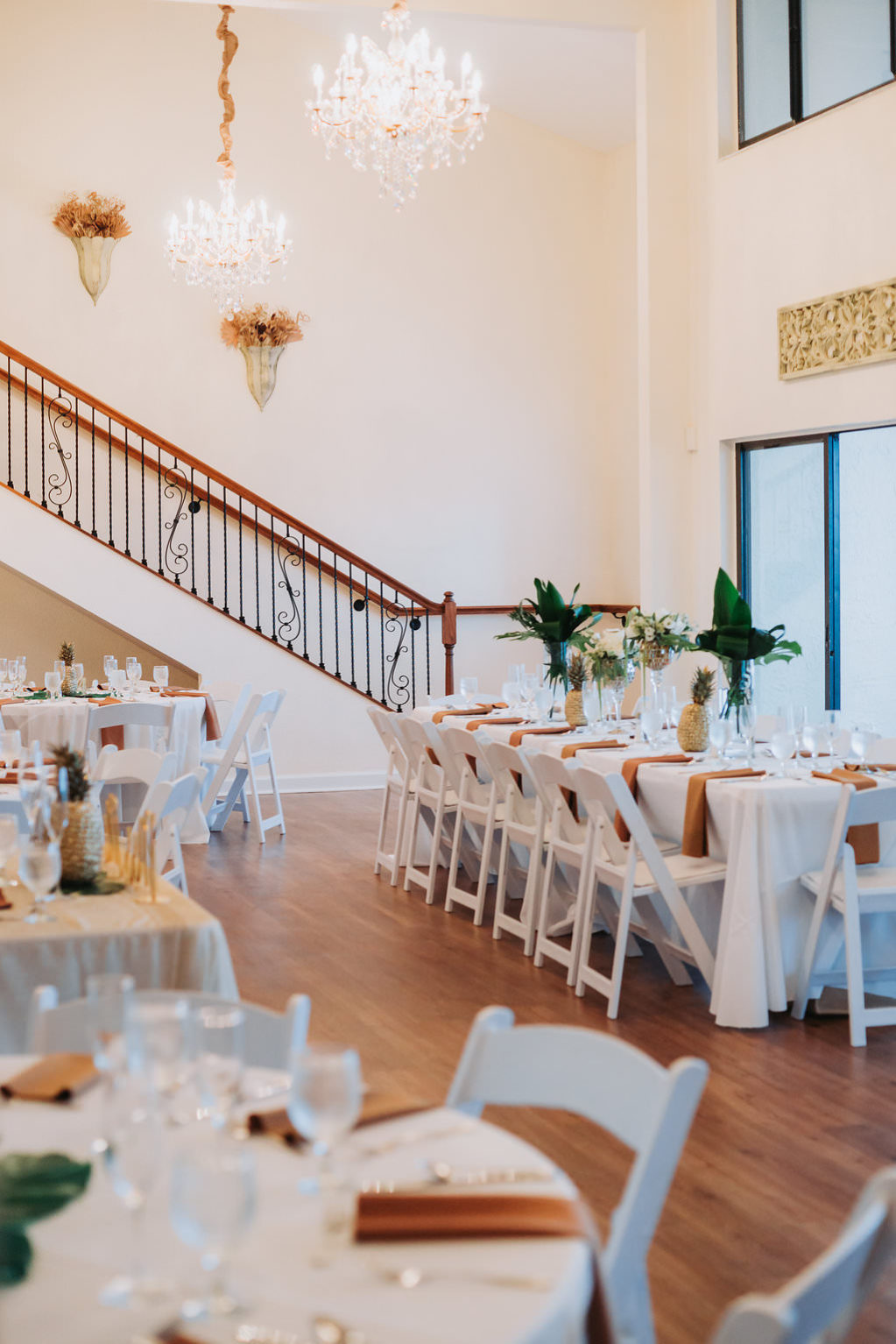 Indoor Hotel Ballroom Wedding Reception with Tan and White Table Linens, Pineapple and Tropical Greenery Centerpieces, and White Folding Chairs | Tampa Bay Waterfront Venue Beso Del Sol