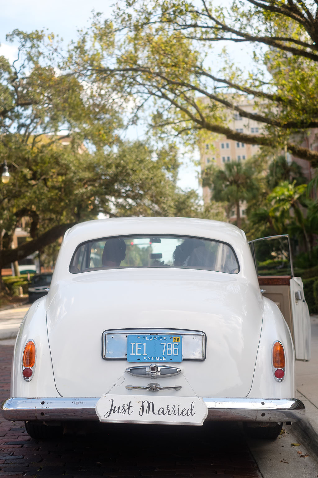 Outdoor Wedding Portrait in Vintage Rolls Royce Car with Hand Painted Black Just Married White Painted Wooden Sign | Tampa Bay Wedding Photographer Marc Edwards Photographs