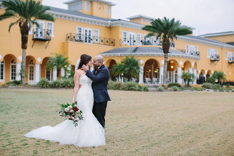 Outdoor Wedding Portrait, Groom in Navy and White Dotted Suit, with Wine Red Rose with Greenery Boutonniere, Bride in Strapless Mermaid Dress with Blush Pink and Red Rose with Greenery Bouquet | Venue Tampa Palms Golf and Country Club | Planner Parties A La Carte