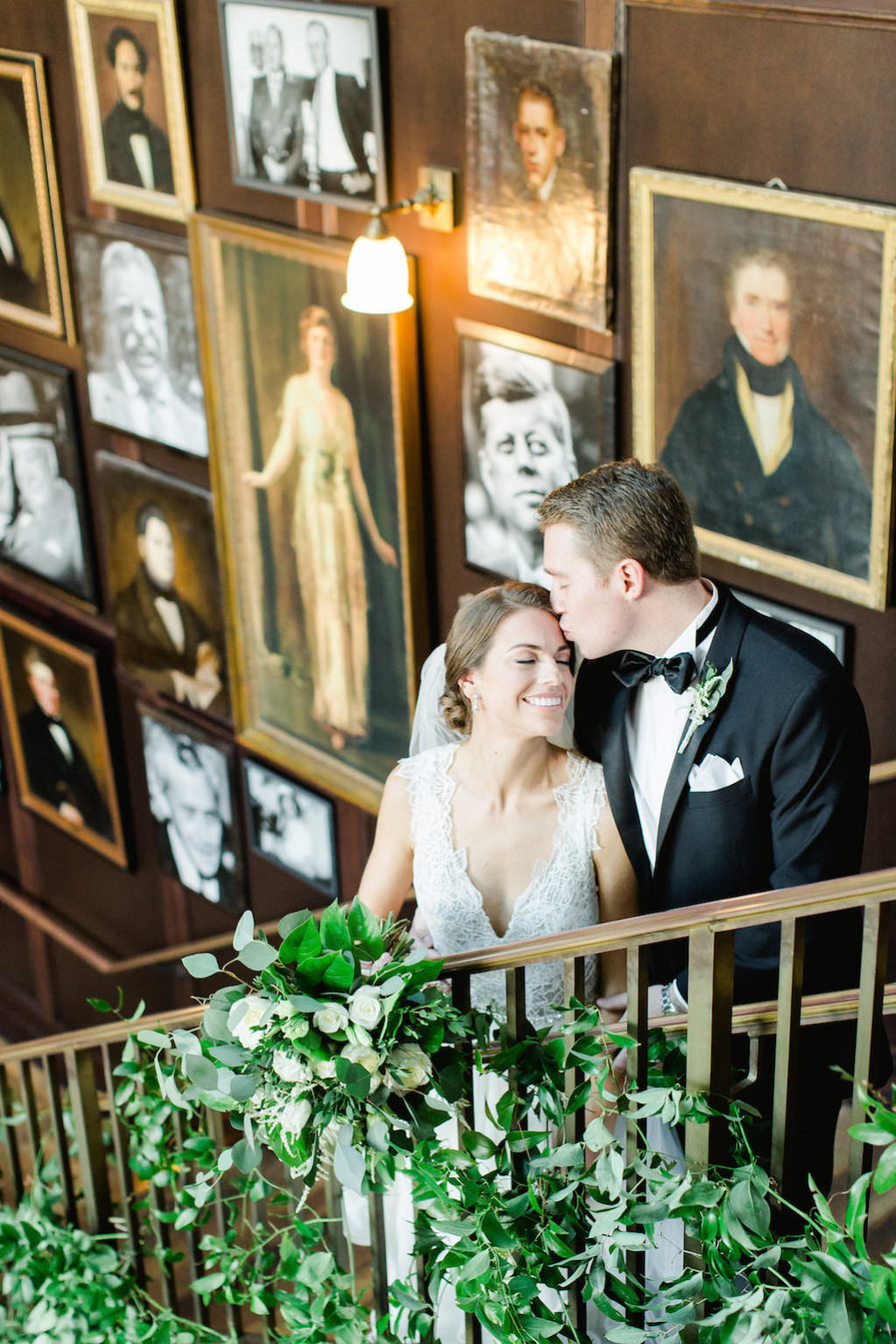 Indoor Wedding Portrait on Staircase with Greenery, Bride in V Neck Dress, Groom in Black Tuxedo | Tampa Wedding Photographer Ailyn La Torre Photography | Downtown Historic Venue The Oxford Exchange