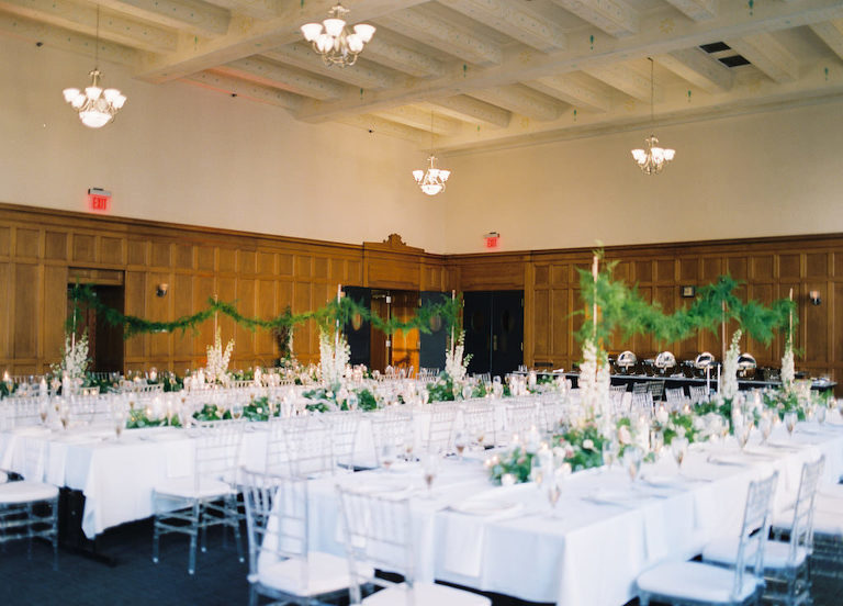 Hotel Ballroom White and Greenery Wedding Reception with Long Feasting Tables, Extra Tall White Spray and Garland Centerpieces, and Clear Chiavari Chairs | Historic Courthouse Downtown Tampa Hotel Venue Le Meridien