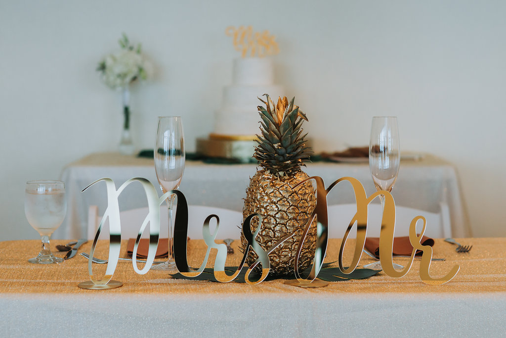 Tropical Wedding Reception Sweetheart Table with Oversized Mr and Mrs Gold Stylish Letters and Gold Painted Pineapple Centerpiece