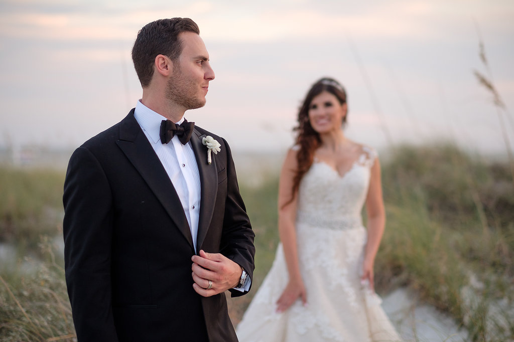 Outdoor Beach Sunset Wedding Portrait, Groom in Black Tux with Bow Tie and White Floral Boutonniere, Bride in Lace Cap Sleeve Belted A Frame Pronovias Dress | Tampa Bay Wedding Photographer Marc Edwards Photographs