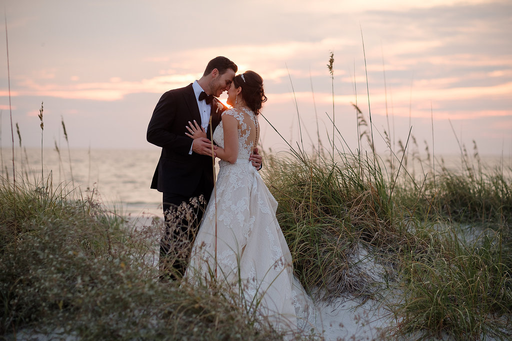 Outdoor Beach Sunset Wedding Portrait, Groom in Black Tux with Bow Tie and White Floral Boutonniere, Bride in Lace Cap Sleeve Belted A Frame Pronovias Dress | Tampa Bay Wedding Photographer Marc Edwards Photographs | St. Pete Beach Historic Hotel Wedding Venue The Don CeSar Hotel