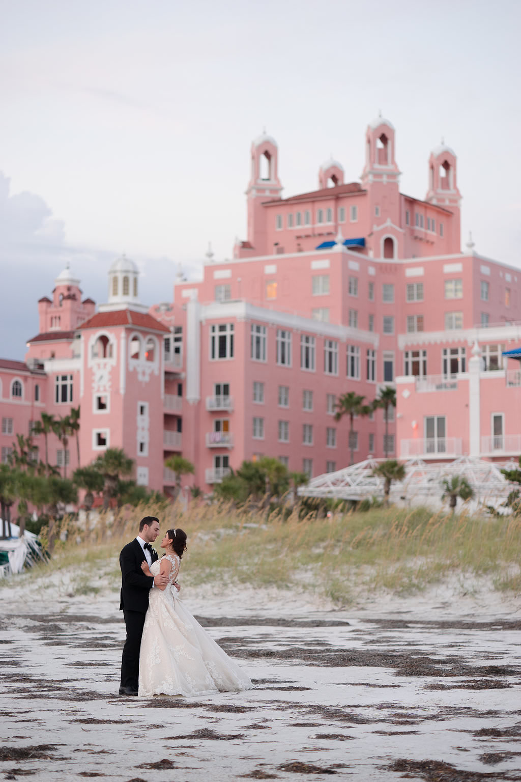 Outdoor Beach Sunset Wedding Portrait, Groom in Black Tux with Bow Tie and White Floral Boutonniere, Bride in Lace Cap Sleeve Belted A Frame Pronovias Dress | Tampa Bay Wedding Photographer Marc Edwards Photographs | St Pete Beach Historic Hotel Wedding Venue The Don CeSar