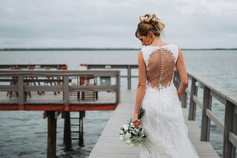 Outdoor Waterfront Bridal Portrait in Illusion Open Back Button Lace Dress with White Rose and Greenery Bouquet | Tampa Bay Wedding Photographer Grind and Press Photography | Dunedin Venue Beso Del Sol