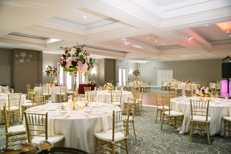 Indoor Country Club Ballroom Wedding Reception with Round Tables and Tall Pink, Wine Red Rose and Greenery Centerpieces in Extra Tall Gold Vases, Candles, Chiavari Chairs and Gold Flatware | Venue Tampa Palms Golf and Country Club | Planner Parties A La Carte | Rentals A Chair Affair and Over The Top Rental Linens