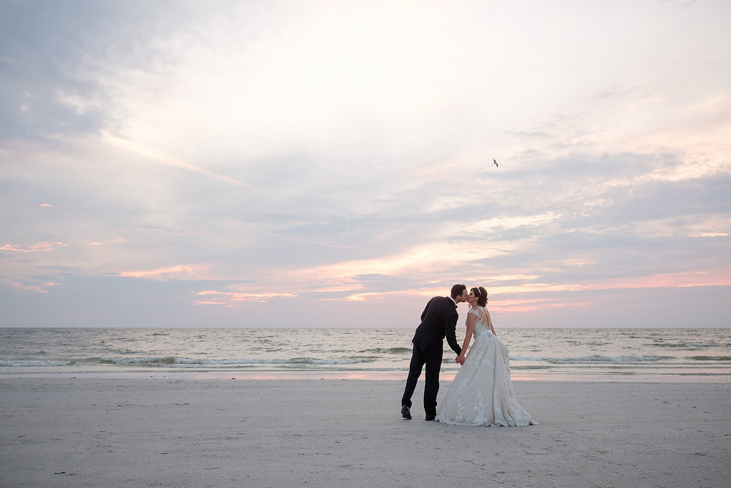 Outdoor Beach Sunset Wedding Portrait, Groom in Black Tux with Bow Tie and White Floral Boutonniere, Bride in Lace Cap Sleeve Belted A Frame Pronovias Dress | Tampa Bay Wedding Photographer Marc Edwards Photographs St Pete Beach Historic Hotel Wedding Venue The Don CeSar