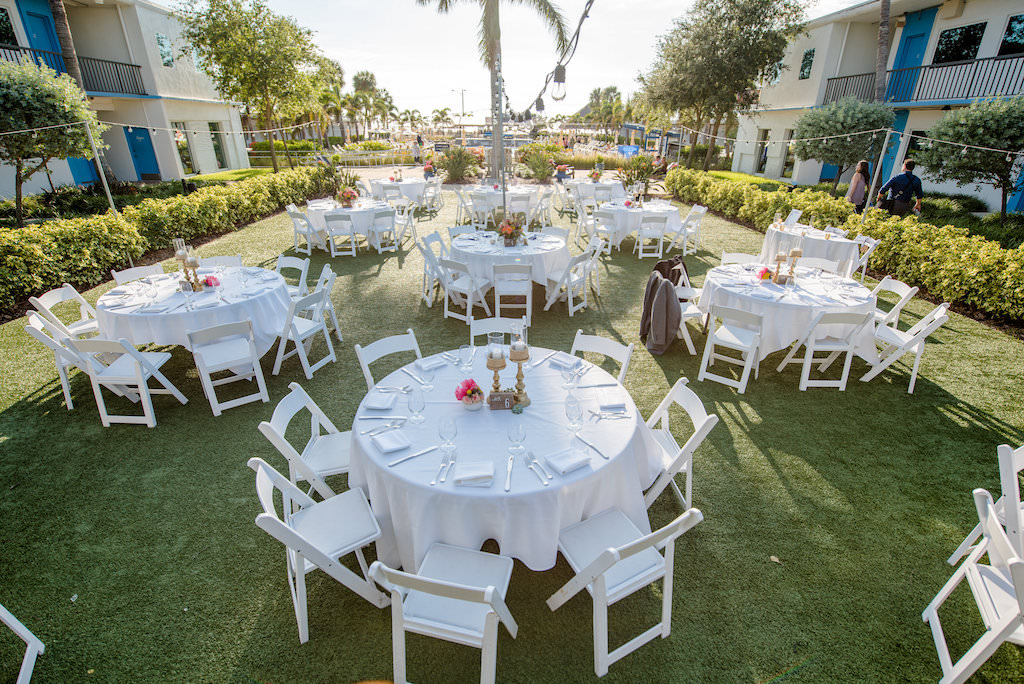 Outdoor Hotel Courtyard Boho Tropical Wedding Reception with Round White LInen Tables and Folding Chairs, Small Pink Floral Centerpieces in White Ceramic Bowls and Gold Candlesticks | St Pete Beach Wedding Venue The Postcard Inn