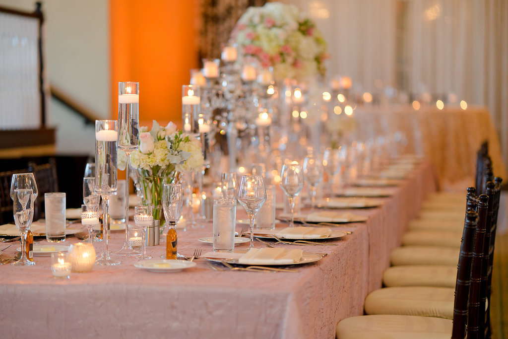 Hotel Ballroom Pink and Champagne Wedding Reception Long Feasting Table with Tall and Low Ivory and Pink Rose Centerpieces with Greenery, Floating Votive Candles in Glass Holders, Black Chiavari Chairs | Textured Linen Rentals from Kate Ryan Linens | Historic Waterfront Hotel Wedding Venue The Don CeSar