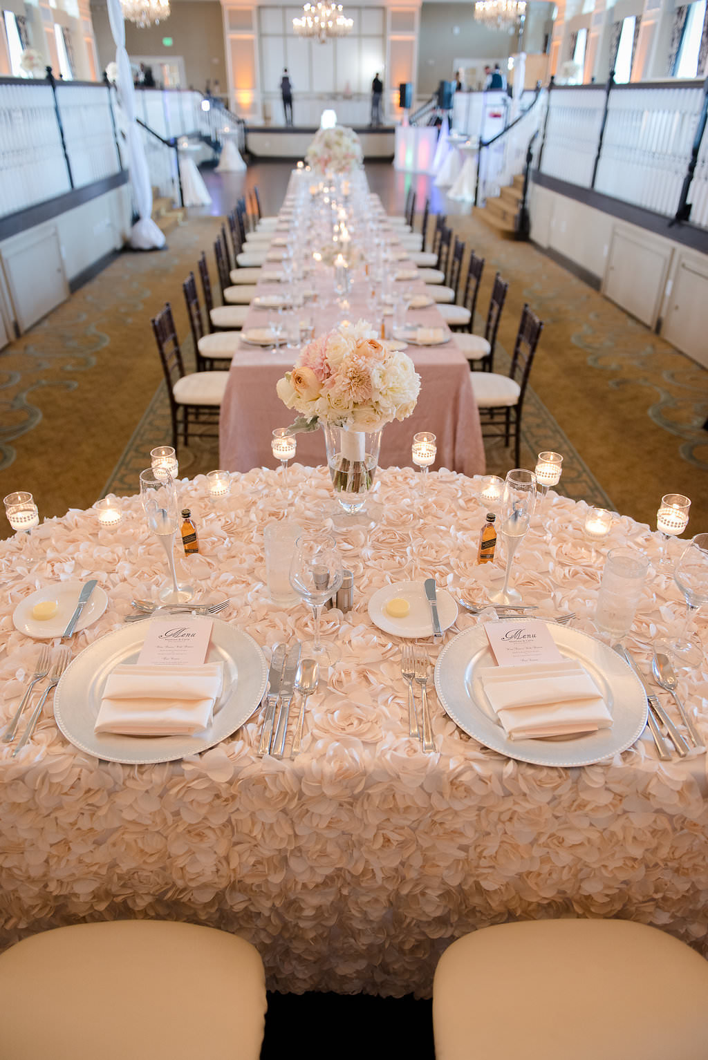 Hotel Ballroom Pink and Champagne Wedding Reception Sweetheart Table with Low Ivory and Pink Rose Centerpiece, Floating Votive Candles in Glass Holders, Black Chiavari Chairs | Textured Linen Rentals from Kate Ryan Linens | Historic Waterfront Hotel Wedding Venue The Don CeSar