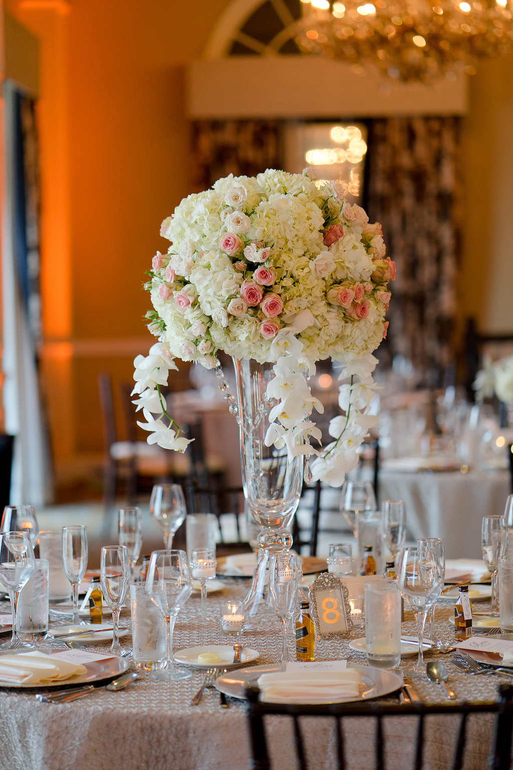 Hotel Ballroom Wedding Reception Round Table with Extra Tall Hydrangea, White ORchid and Pink Rose Centerpiece in Glass Vase, Gold Table Number, Mini Liquor Bottle Favor, Black Chiavari Chairs | Champagne Textured Linen Rentals Kate Ryan Linens | Historic St Pete Beach Hotel Wedding Venue The Don CeSar