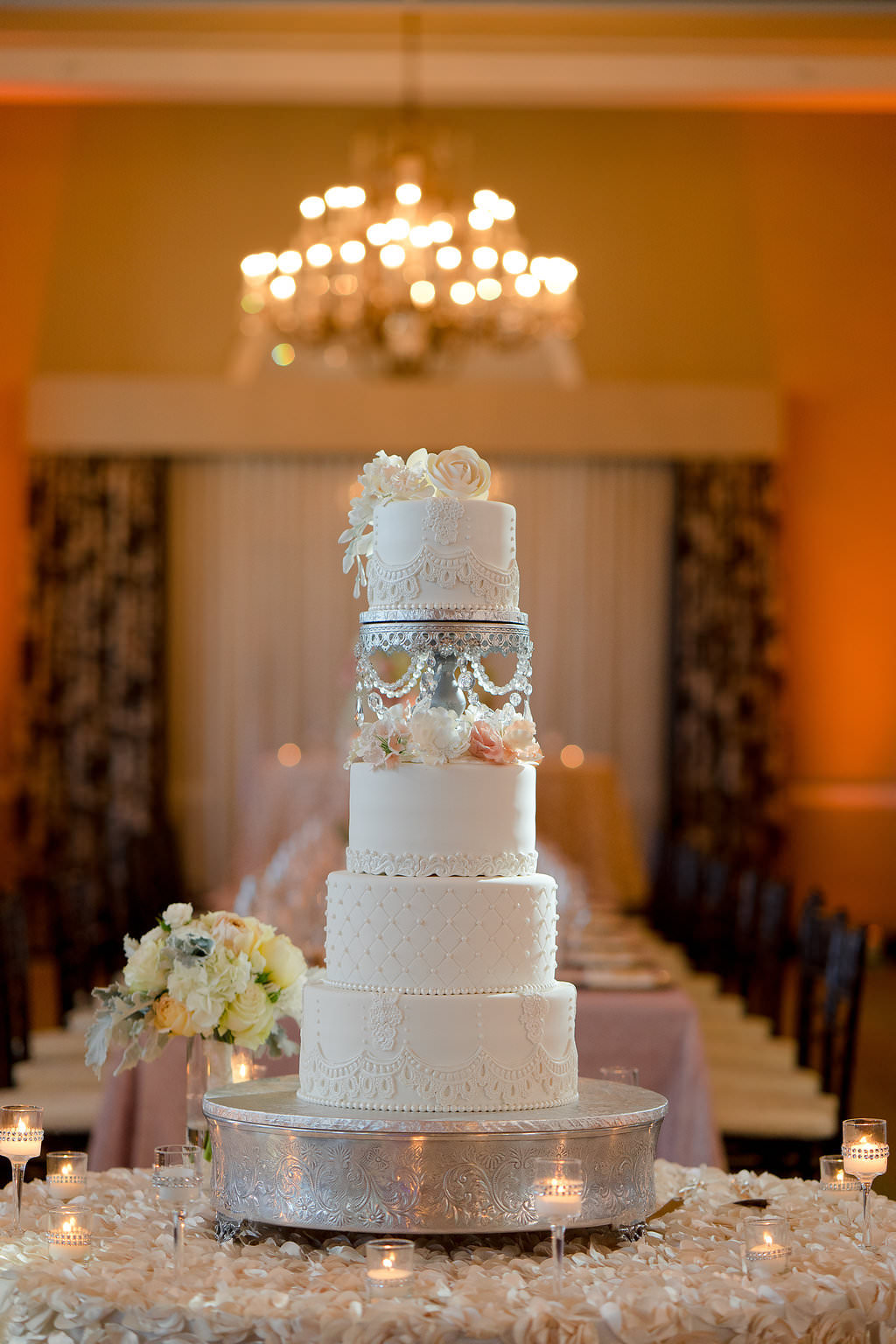 Four Tier Round White Wedding Cake with Silver Cake Stand and Blush PInk Roses on Textured Linen with Candles | Tampa Bay Textured Wedding Linen Rentals Kate Ryan Linens | Hotel Ballroom Reception Venue The Don CeSar