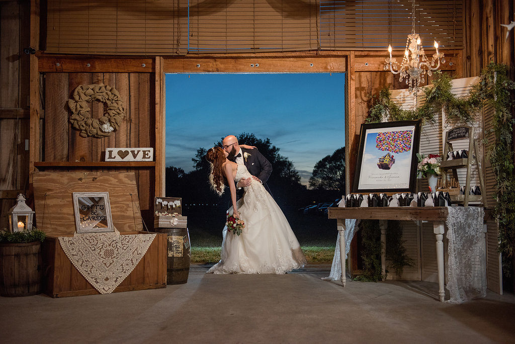 Bride and Groom Portrait at Barn Wedding Reception with Favor Table with Framed Disney Up Movie Poster, and Black and White Favors, with Vintage Chandelier, Wooden Table and dTrunk with Lace, Lantern, and Greenery Garland | Tampa Bay Venue Wishing Well Barn