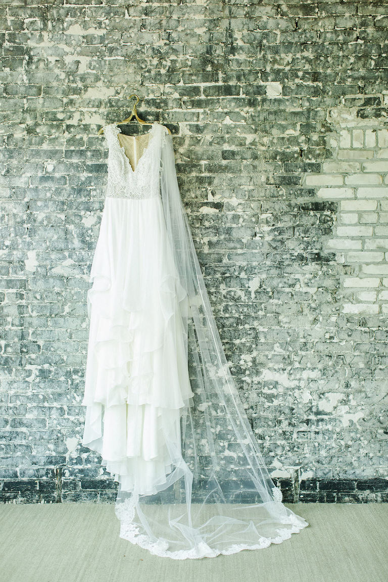 Lace Bodice Hayley Paige Wedding Dress with Veil on Hanger and Brick Wall