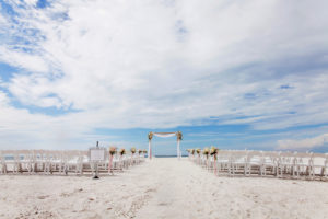 Outdoor Beach Wedding Ceremony decor with White Folding Chairs, White Floral with Pink Ribbon and Draping, Bamboo Ceremony Arch, and Framed Welcome Sign | Tampa Bay Waterfront Hotel Wedding Venue Hilton Clearwater Beach | Rentals A Chair Affair