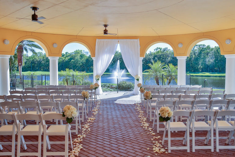 Outdoor Covered Courtyard Wedding Ceremony with White Draping Ceremony Arch, White Folding Chairs, Flower Petal Aisle and White and Blush Pink Floral with Greenery | Tampa Bay Wedding Rentals and Florist Gabro Event Services | Venue Tampa Palms Golf and Country Club