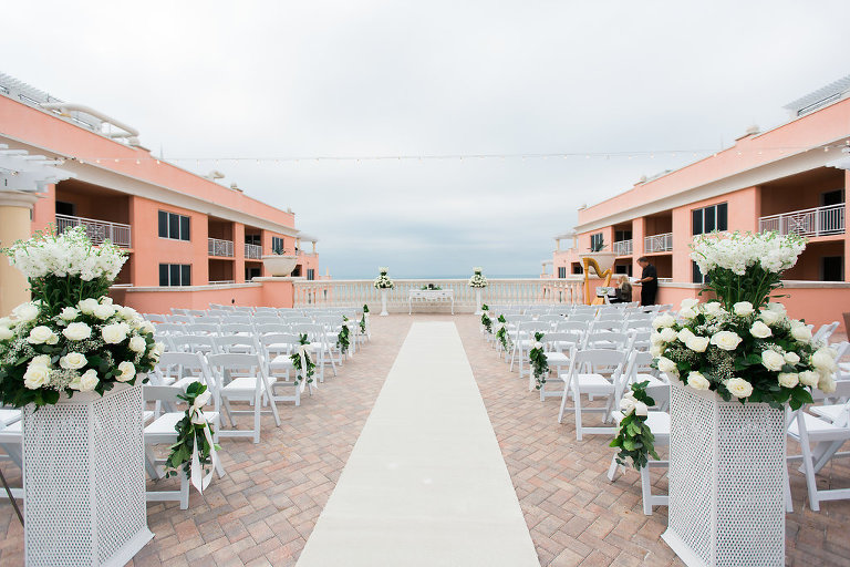 Waterfront Hotel Rooftop Elegant Wedding Ceremony with White Folding Chairs, White Rose and Greenery Floral Arrangements, and Fabric Aisle | Venue Hyatt Regency Clearwater Beach | Tampa Bay Wedding Planner Special Moments Event Planning | Florist Apple Blossoms Floral Designs