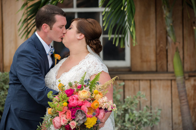 Outdoor First Look Portrait, Bride in Lace Cap Sleeve Dress with PInk and Orange Tropical Bouquet with Greenery and Striped Ribbon, Groom in Navy Suit with Boutonniere   St Pete Wedding Photographer Caroline and Evan Photography   Tampa Bay Wedding Dress Shop Truly Forever Bridal