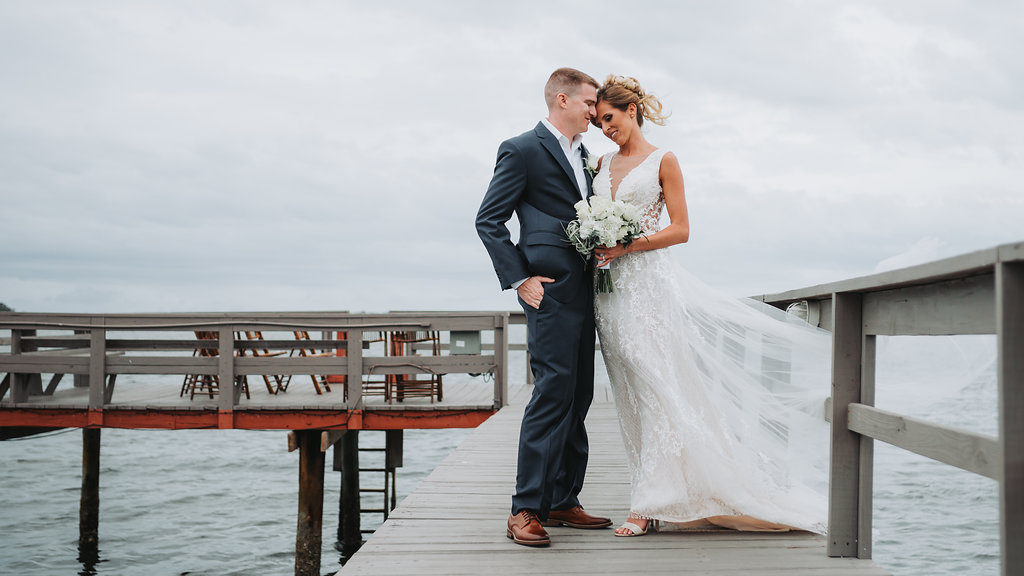 Outdoor Waterfront Wedding Portrait, Groom in Blue Suit with White Rose Boutonniere, Bride in Cutout V Neck Lace Dress with White Rose and Greenery Bouquet | Tampa Bay Wedding Photographer Grind and Press Photography | Dunedin Venue Beso Del Sol
