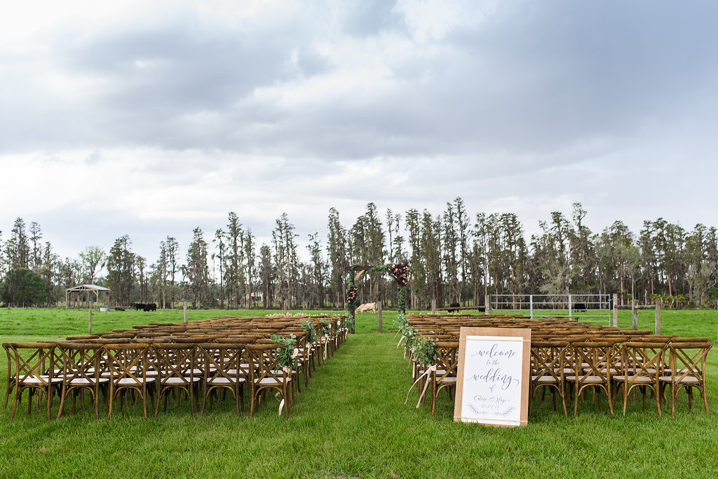 OUtdoor Farm Wedding Ceremony with Wooden Crossback Chairs, White Protea and Greenery Florals, and Wooden and White with Stylish Navy Blue Printed Welcome Sign, and Wooden Ceremony Arch with Marsala Red and Blush Pink Florals   Tampa Bay Wedding Planner NK Productions