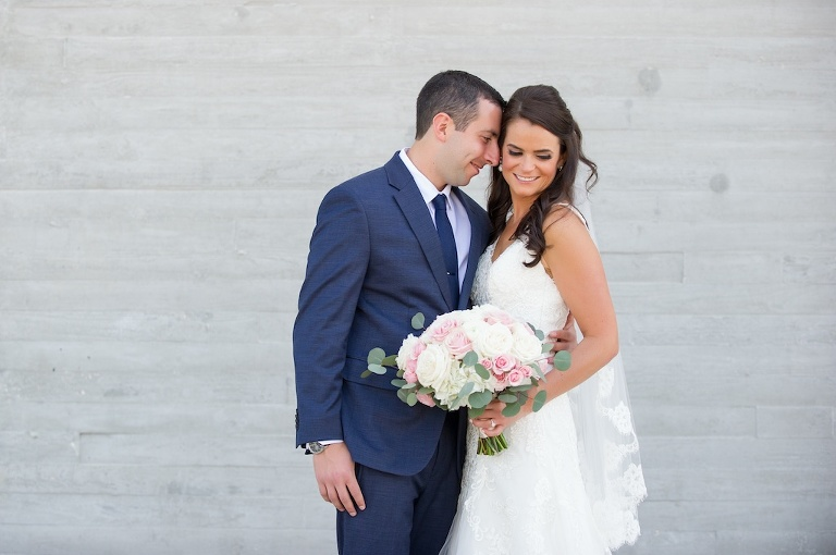 Outdoor Downtown Wedding Portrait, Bride in Sweetheart A Line Wedding Dress with Long Lace Edged Comb Veil and White and Pink Rose with Greenery Bouquet, Groom in Navy Blue Suit | Tampa Wedding Photographer Andi Diamond Photography