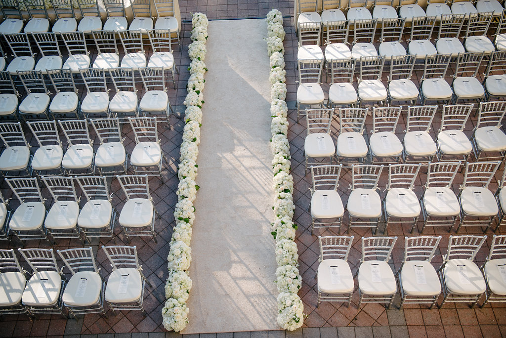 Elegant Outdoor Courtyard Wedding Ceremony with Silver Chiavari Chairs and White Floral lined Wedding Ceremony Aisle