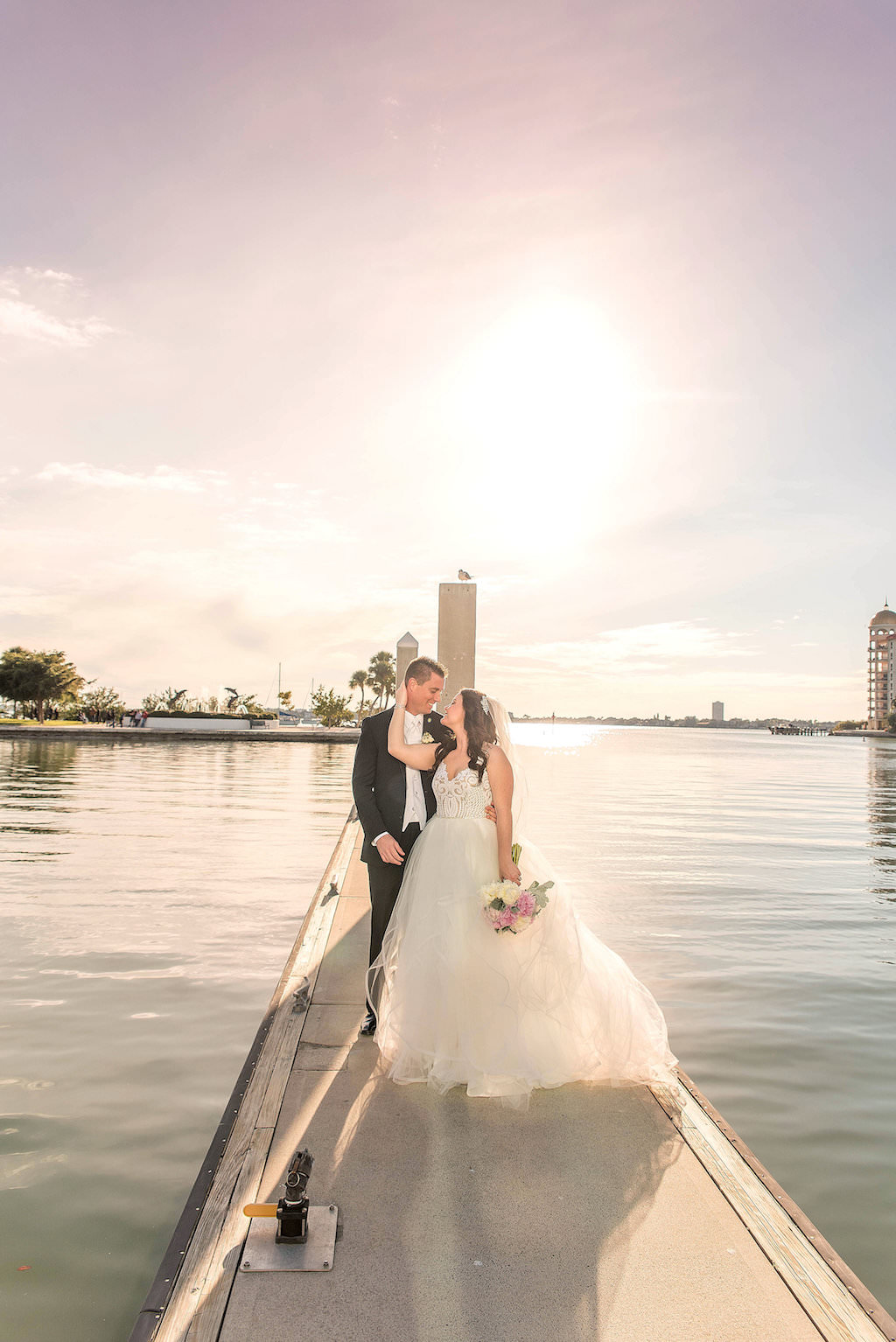 Outdoor Waterfront Marina Sunset Wedding Portrait, Bride in Layered Ballgown Hayley Paige Dress with Veil with PInk and White Peony Bouquet | Sarasota Wedding Photographer Kristen Marie Photography
