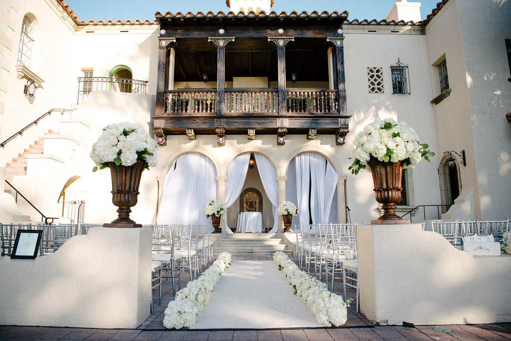Elegant Outdoor Courtyard Wedding Ceremony with Silver Chiavari Chairs and White Floral lined Wedding Ceremony Aisle, White Draped Backdrop, and Large Classical Copper Planters with Hydrangea and Greenery | Sarasota Historic Wedding Venue Crosley Powel Estate