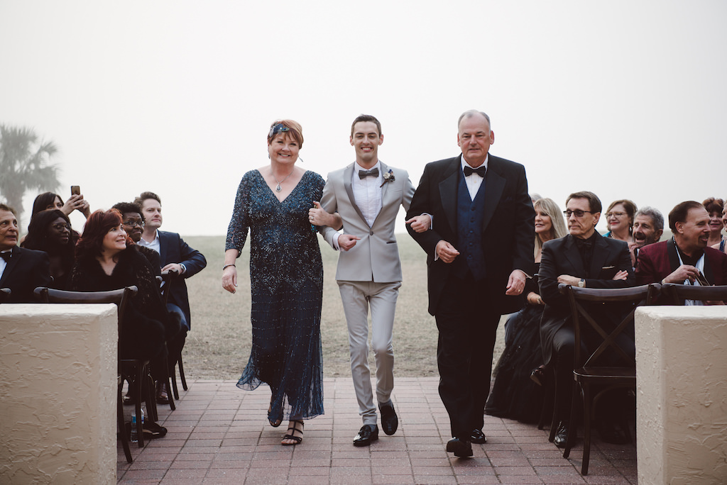 1920s Vintage Glam Inspired Same Sex Wedding Ceremony Portrait, Groom in Light Gray Tuxedo with Paper Flower Boutonniere, Parents of the Groom in Teal, with Black Cross Back Chairs