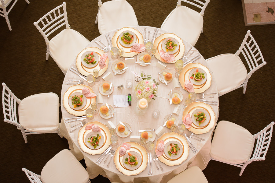 Elegant Romantic Wedding Reception Round Table with White Linen, Pink Napkins, Gold Chargers and Citrus Salads with Pink, White and Greenery Small Centerpiece and Chiavari Chairs | Tampa Wedding Caterer Olympia Catering