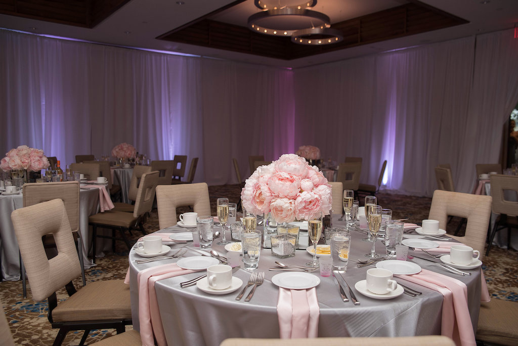 Modern Indoor Pink and Gray Wedding Reception Round Tables with with Satin Table Linens, Low Peony Centerpiece in Square Mirror Vase, with Modern Square Chairs and Purple Uplighting | Downtown Sarasota Wedding Venue The Francis